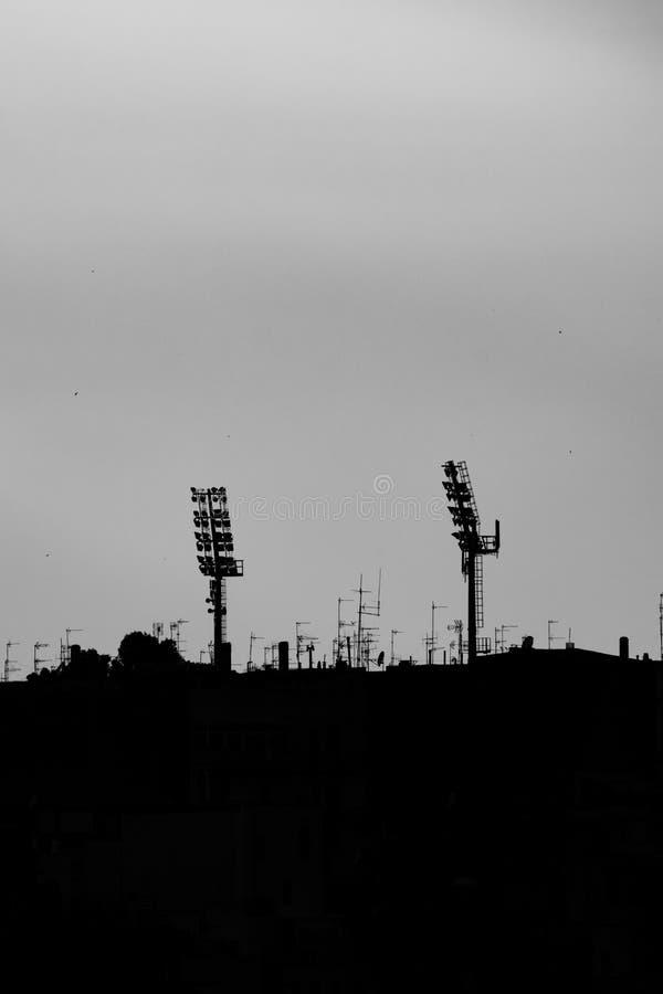 Konturer av två sportstadionljus på solnedgången royaltyfria foton