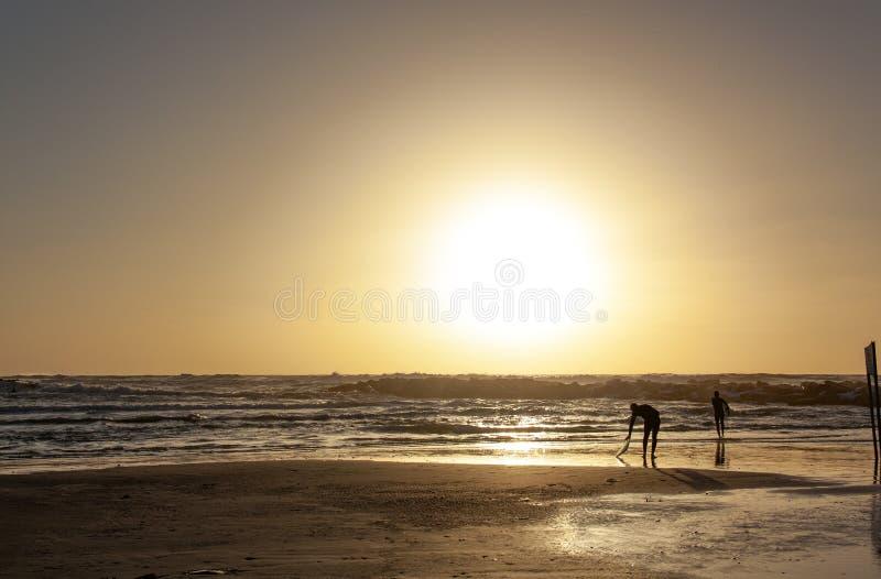 Konturer av två surfare på solnedgången på stranden arkivbilder