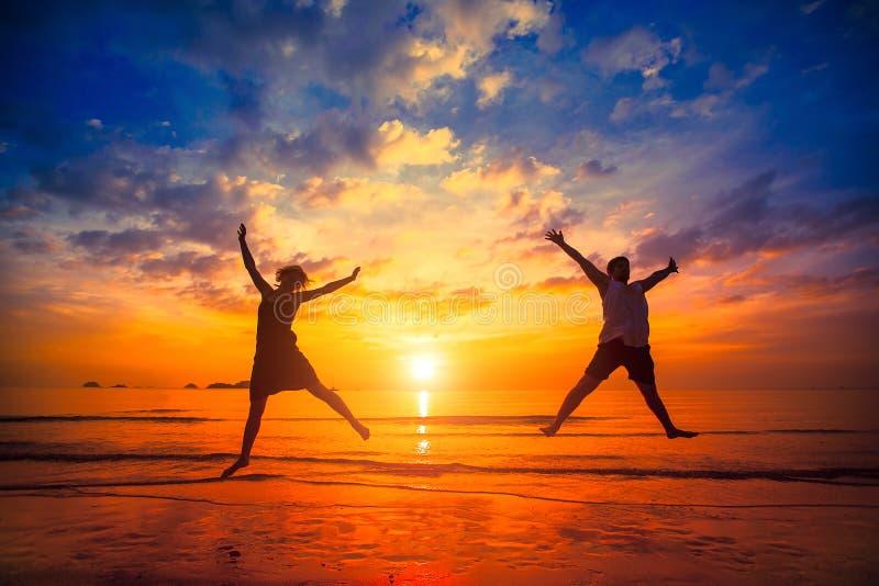 Konturer av ungdomarsom hoppar på solnedgången på havsstranden Lyckligt royaltyfria bilder