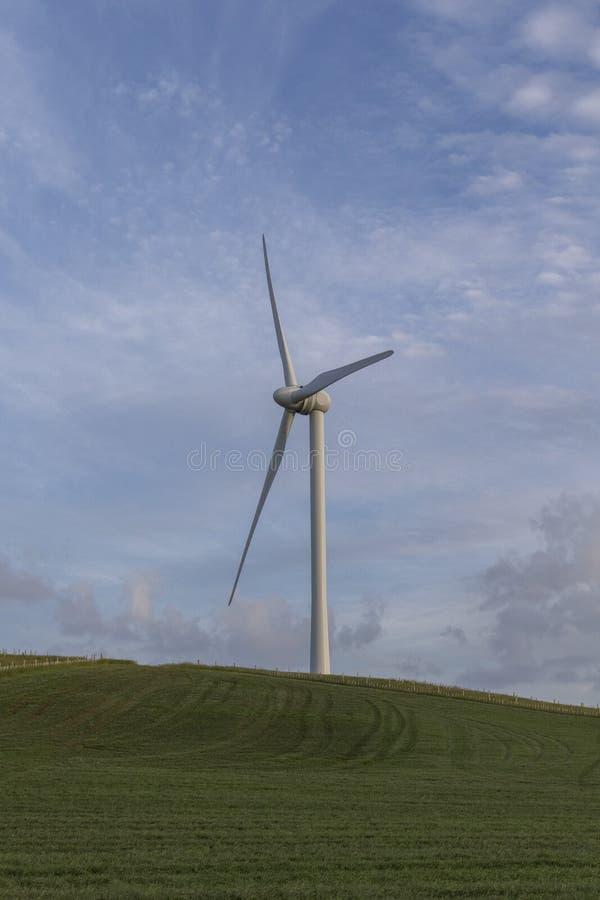 Konturer för en vindturbin i ett fält med en blå himmel royaltyfria bilder