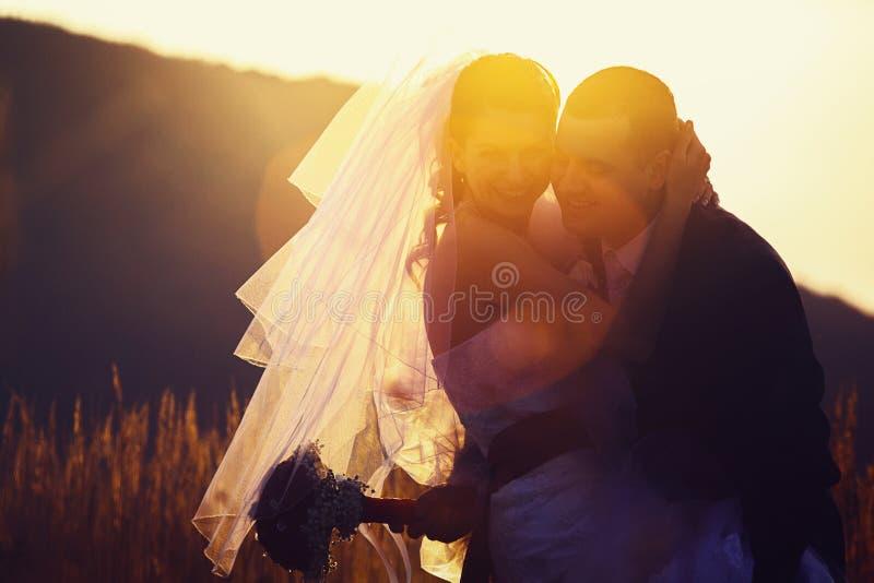 Konturerna av nygifta personer som står på fältet i det soligt royaltyfria bilder