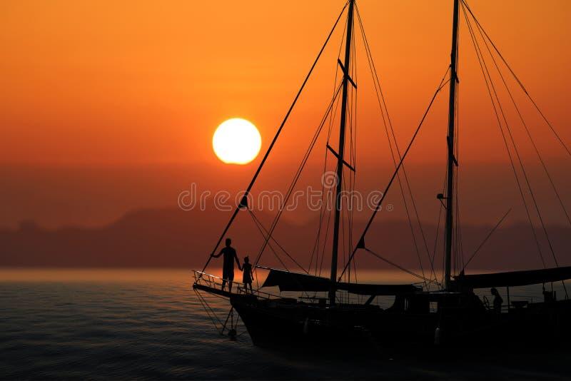 Konturfamilj på yachten med röd himmelsolnedgång royaltyfria foton