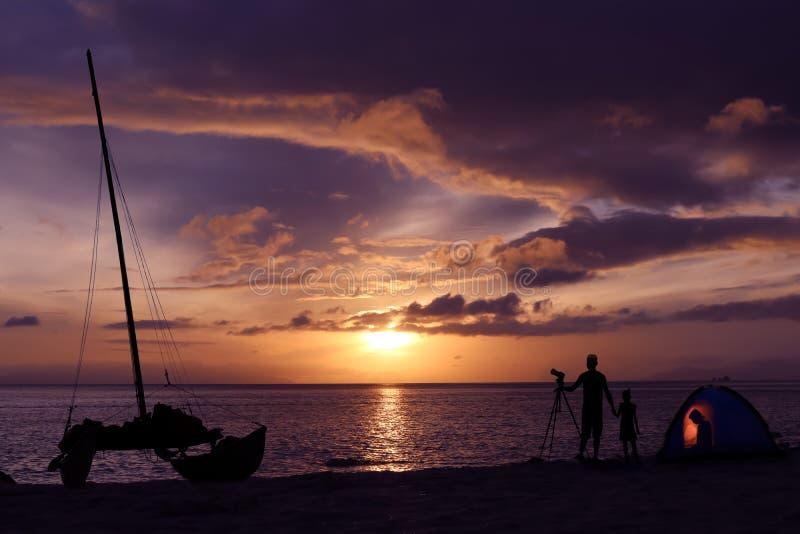 Konturfamilj som campar på stranden med segelbåten fotografering för bildbyråer