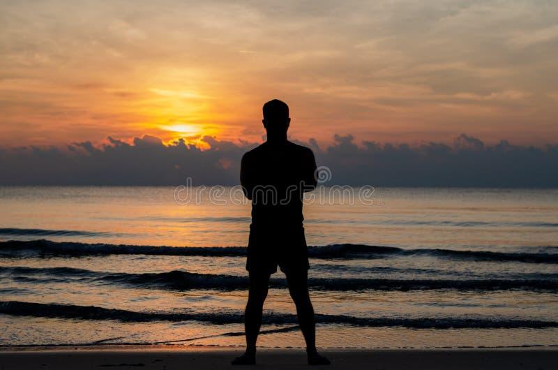 Konturfotoet av en man som bara står på stranden, tycker om soluppgångögonblick royaltyfri bild