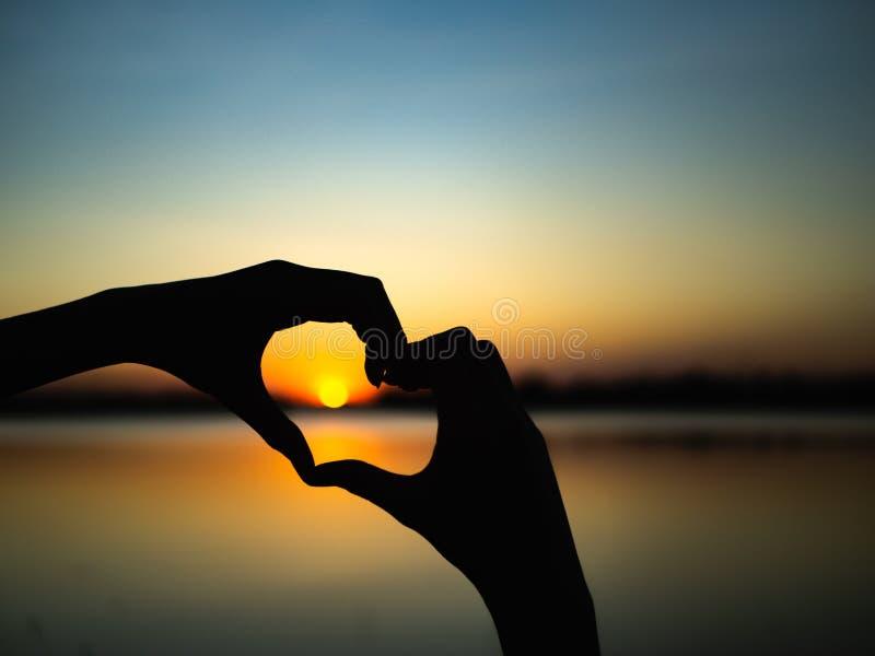 Konturhänder som är hjärtaform på solnedgångbakgrund Lyckligt förälskelse, idé för dag för valentin` s, tecken, symbol, begrepp arkivfoto