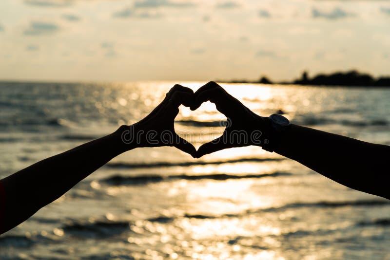Konturhanden i hjärtaform med soluppgång i mitt och är royaltyfri foto