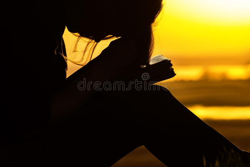 Konturkvinna som ber till guden i naturen på solnedgången, begreppet av religionen och andlighet royaltyfri foto