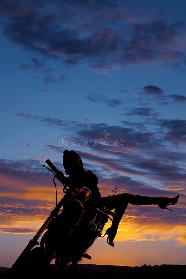 Konturkvinnan på motorcykelbenet head upp tillbaka sidan arkivfoton