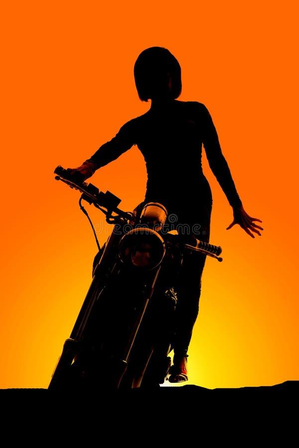 Konturkvinnan på motorcykelställningsframdel räcker ner arkivbilder