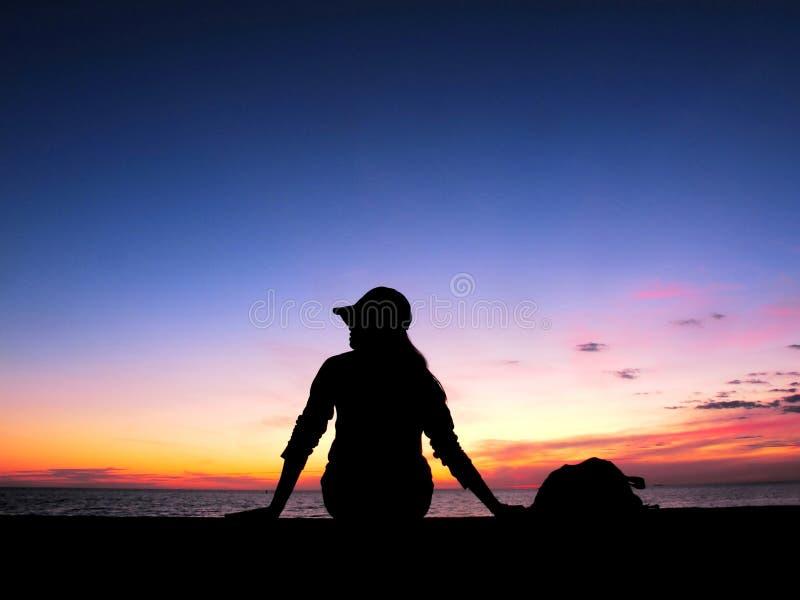 Konturkvinnan sitter på havet, solnedgångljus royaltyfria foton
