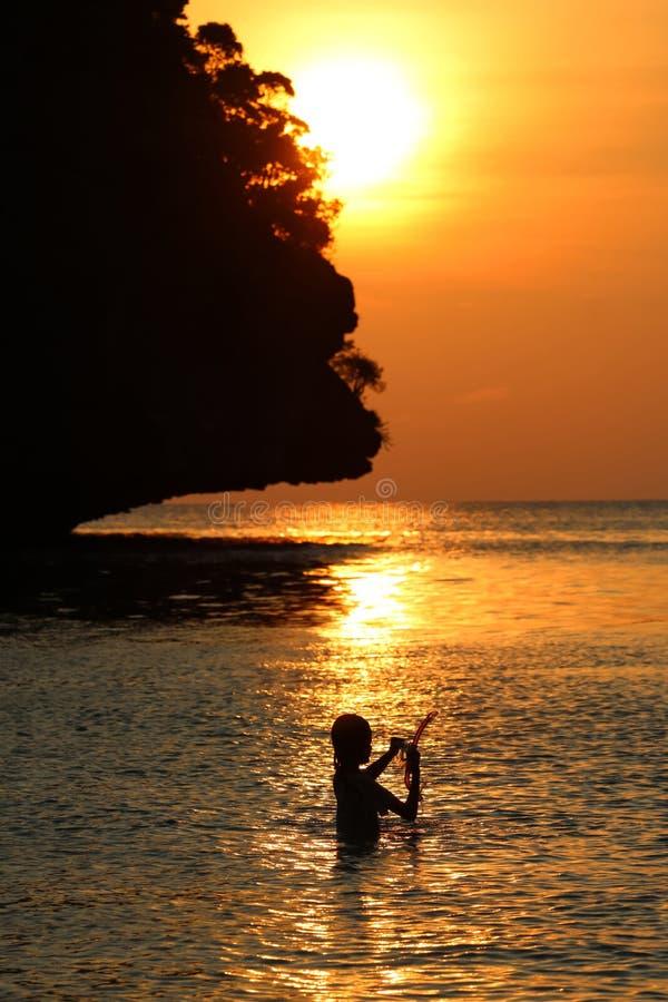 Konturliten flicka att tycka om simma och snorkla nära stranden med röd himmel och solnedgång royaltyfria bilder