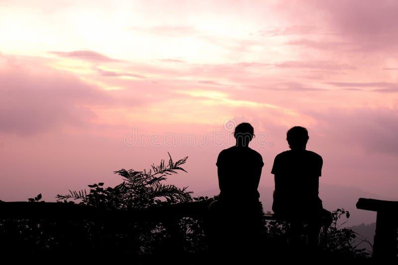 Konturman- och kvinnasammanträde håller ögonen på aftonhimlen på den purpurfärgade solnedgången royaltyfri foto