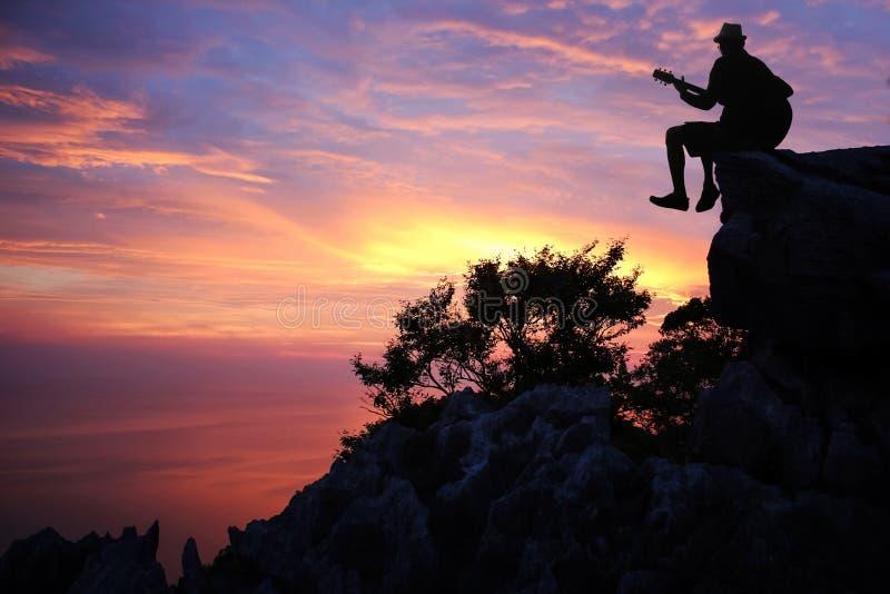 Konturman som spelar en gitarr på berget arkivbild