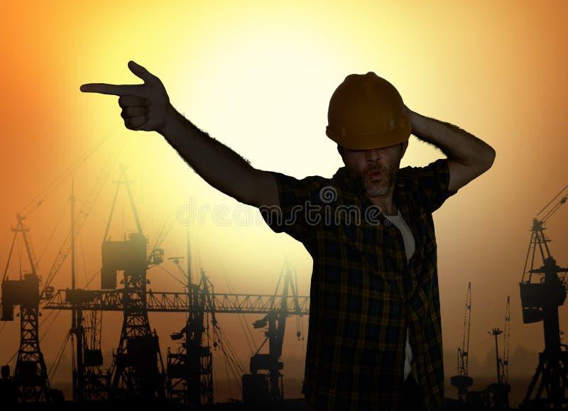 Konturn av arbetaren som dansar lycklig tävlan med popstjärnan för den hårda hatten, poserar att fira arbetsdag är över på hamnkr royaltyfri fotografi