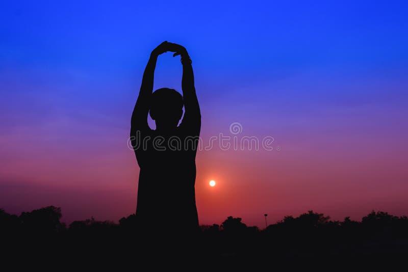Konturn av att meditera för man och yoga som öva med övning på soluppgång parkerar offentligt, morgon arkivfoto