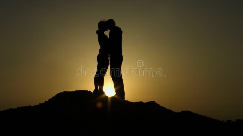 Konturn av barn kopplar ihop förälskat krama och att kyssa i solnedgångstrålar på berget royaltyfria foton