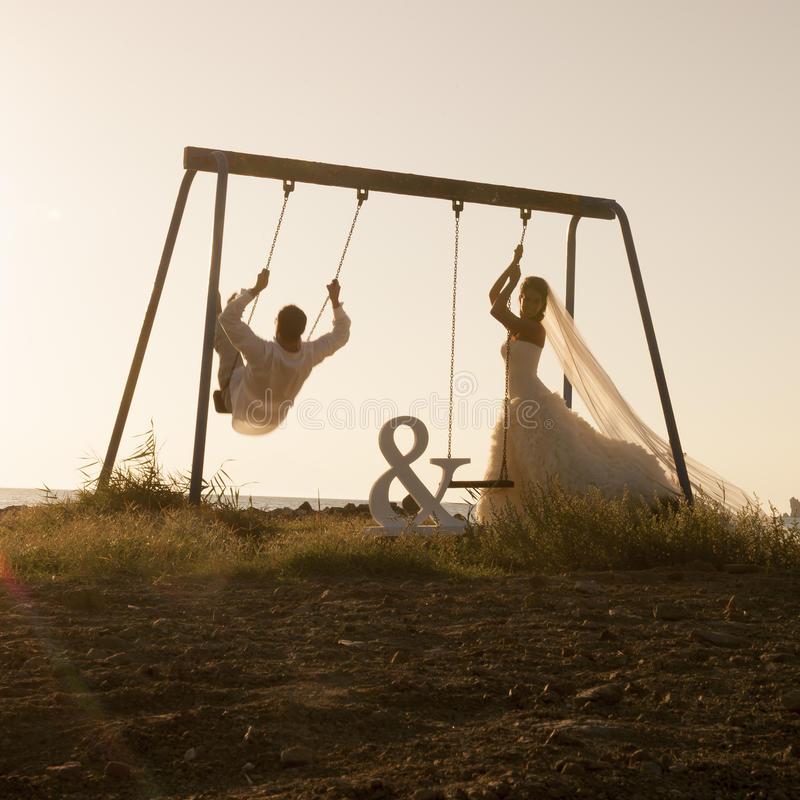Konturn av barnpar som spelar på gunga, ställde in på solnedgången royaltyfria bilder