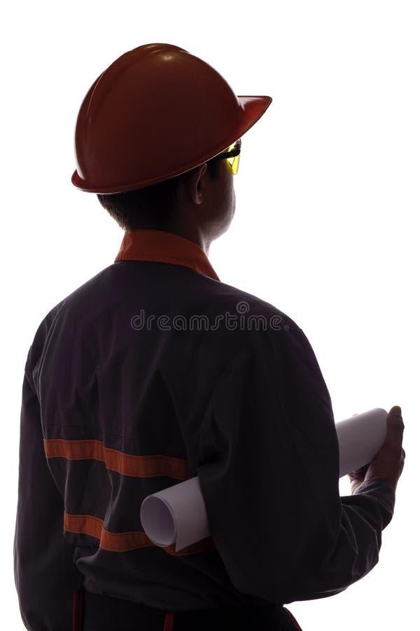 Konturn av byggnadsarbetaren med projekt i händer, man i overaller i hård hatt och säkerhetsexponeringsglas på vit isolerade back arkivbild