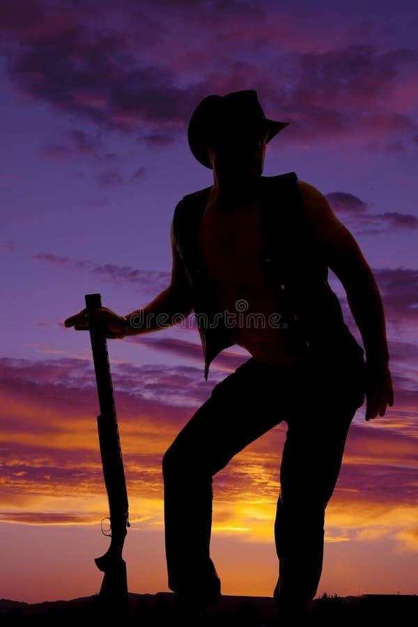 Konturn av cowboyen med den roliga hagelgeväret poserar i solnedgång arkivfoton
