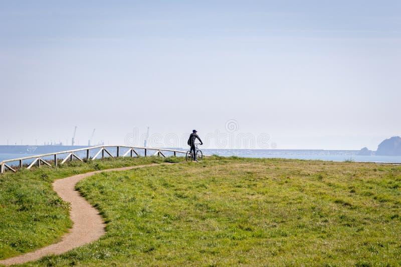 Konturn av cyklisten på vägcykeln på middagsporten och aktiv tid för livbegreppssolnedgång En manridning på cykeln i en parkera royaltyfri foto