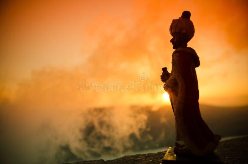 Konturn av den arabiska mannen står bara, i öknen och att hålla ögonen på solnedgången med moln av dimma Östlig saga fotografering för bildbyråer