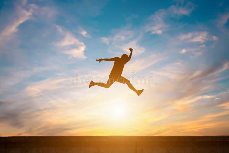 Konturn av den lyckliga mannen hoppar på vägen royaltyfri foto