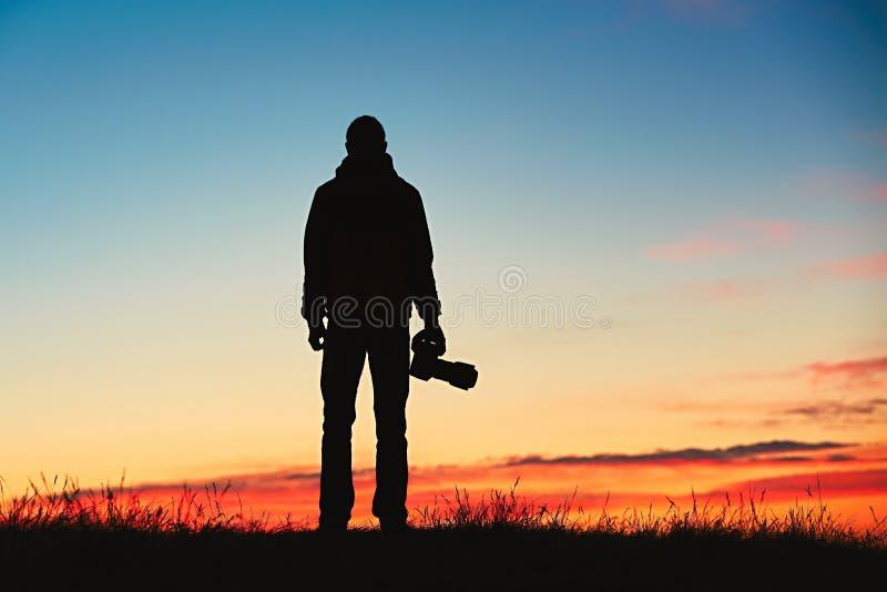 Konturn av den unga fotografen tycker om solen Fotograf på soluppgången arkivbild