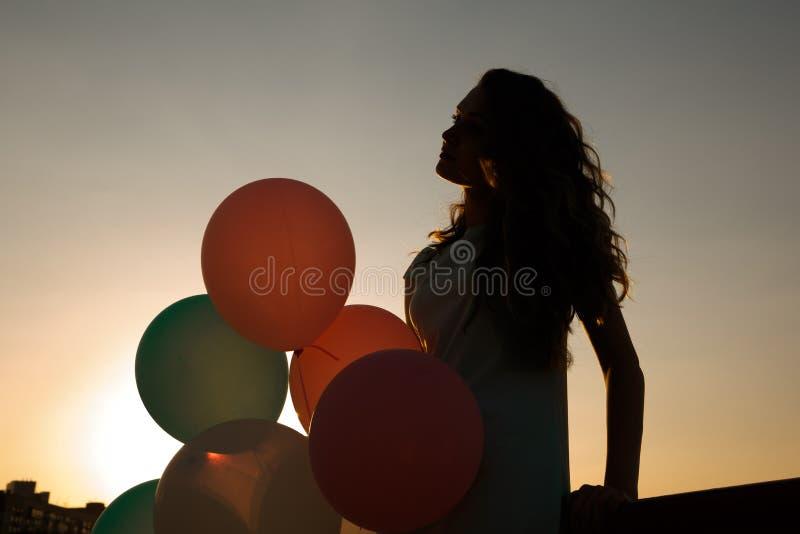 Konturn av den unga kvinnan med flyg sväller mot himlen fotografering för bildbyråer