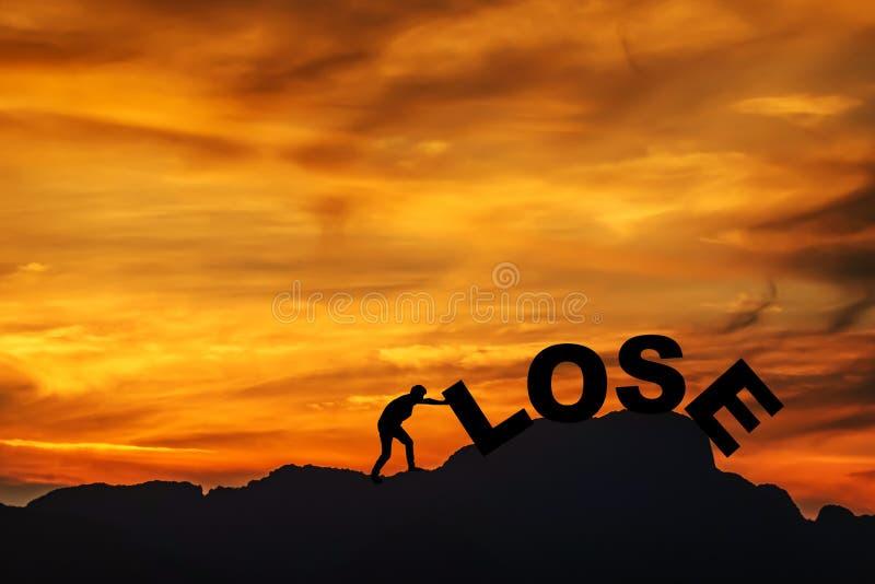 Konturn av den unga mannen som kämpar för att skjuta en text av, förlorar, medan klättra på den klippa-, himmel- och solljusbakgr royaltyfria bilder