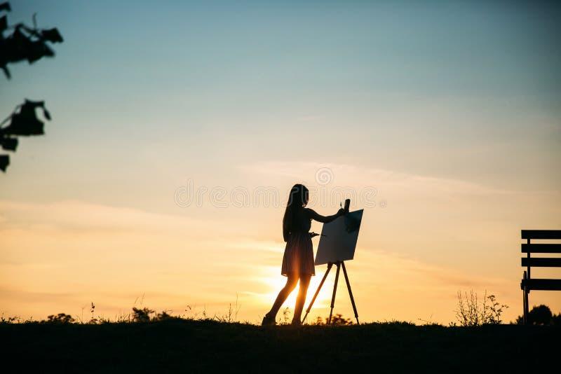 Konturn av en blond flickakonstnär Lady målar en målning på kanfasen med hjälpen av målarfärger Träuppehällen för en staffli royaltyfri bild
