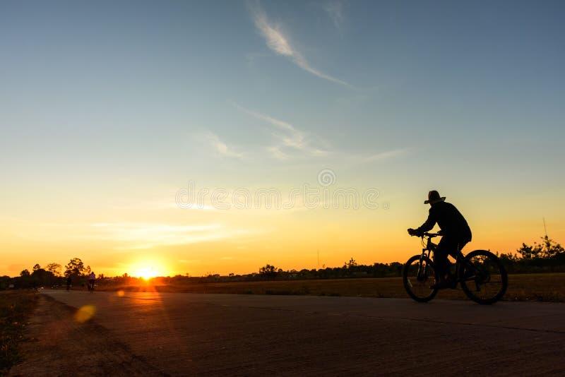 Konturn av en gamal man som rider en cykel på solnedgången parkerar offentligt royaltyfri fotografi