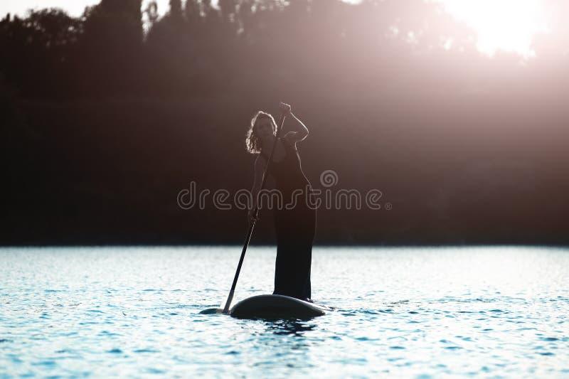 Konturn av en härlig kvinna står på upp skovelbrädet SUP04 royaltyfria bilder