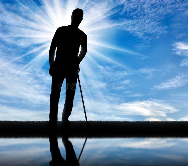 Konturn av en handikappade personerman stöttar sig med en krycka nära floden royaltyfria foton
