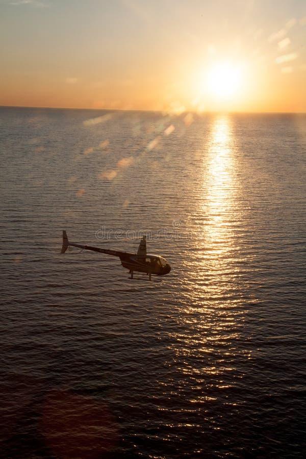 Konturn av en helikopter mot det mörka solnedgånghavet arkivbild