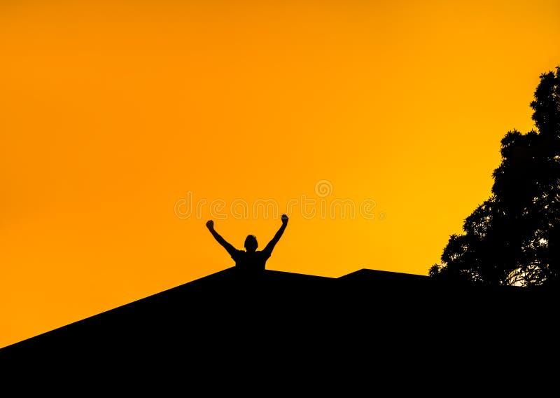 Konturn av en man med händer lyftte i solnedgången Manen taklägger på royaltyfria bilder