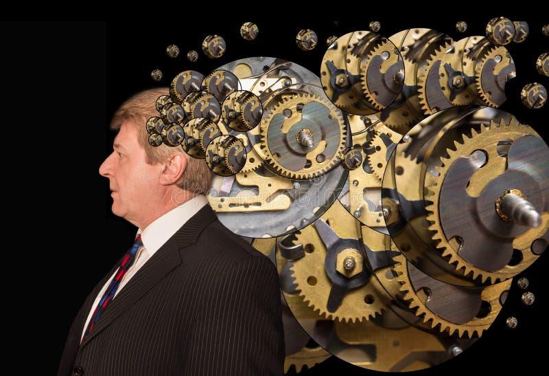 Konturn av en man med en hjärna utgjorde av kugghjul, eller kuggemaskinen särar arbeten royaltyfri fotografi