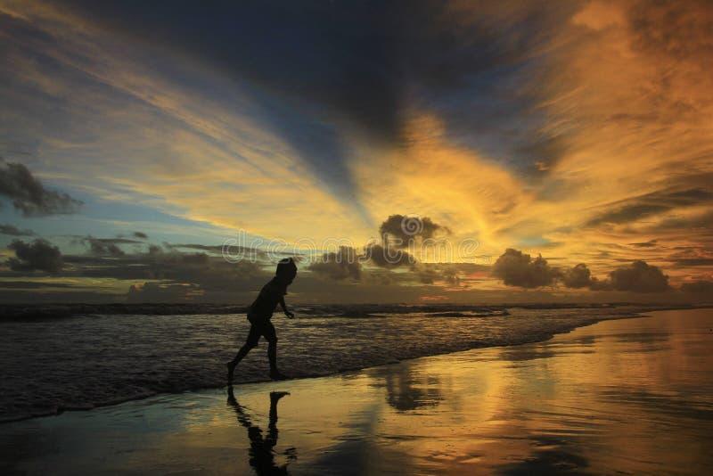 Konturn av en pojkespring som undviker stranden, vinkar på skymning med en dramatisk himmelbränning arkivfoton