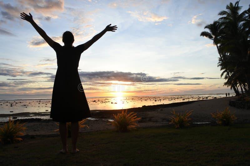 Konturn av en turist- kvinna tycker om dramatisk solnedgång arkivbild