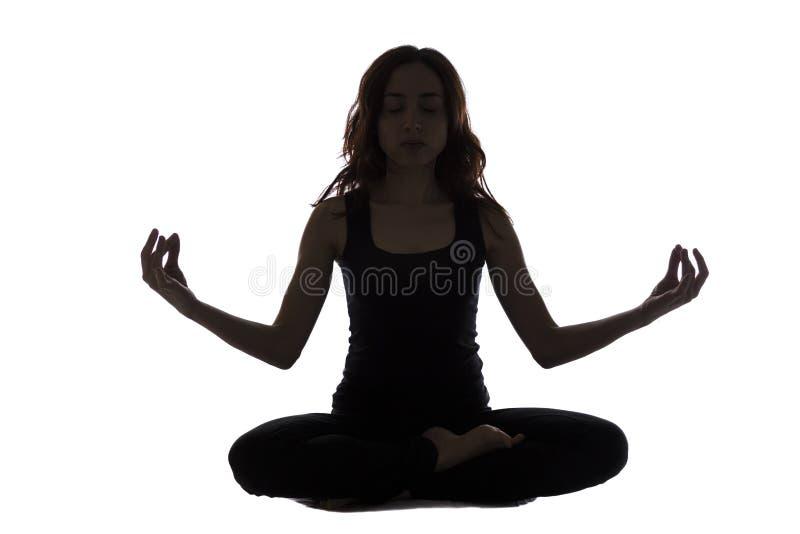 Konturn av en ung kvinna i meditation poserar fotografering för bildbyråer