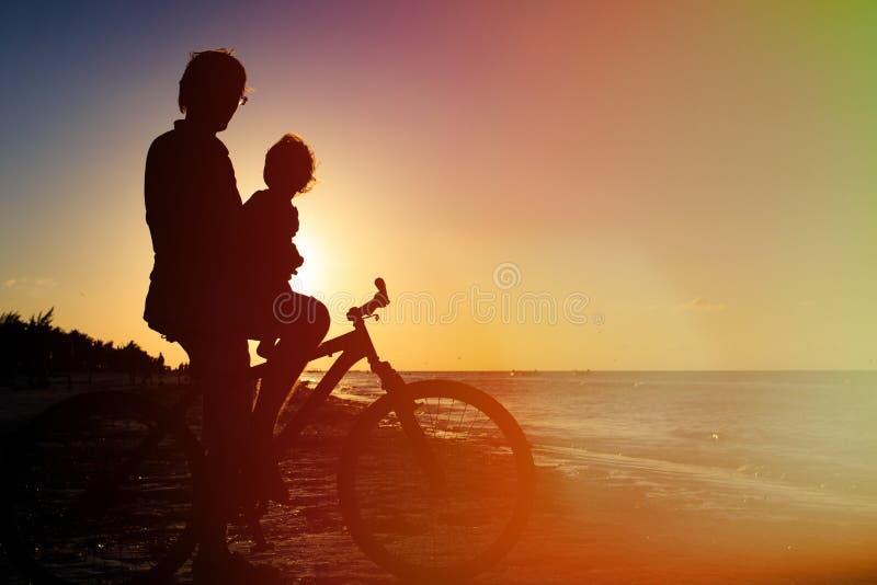 Konturn av fadern och behandla som ett barn att cykla på solnedgången fotografering för bildbyråer