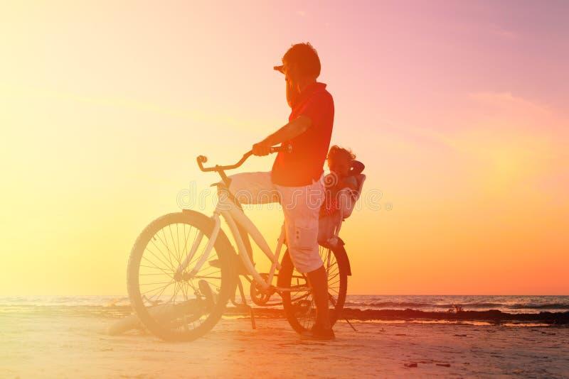 Konturn av fadern och behandla som ett barn att cykla på solnedgången arkivbilder