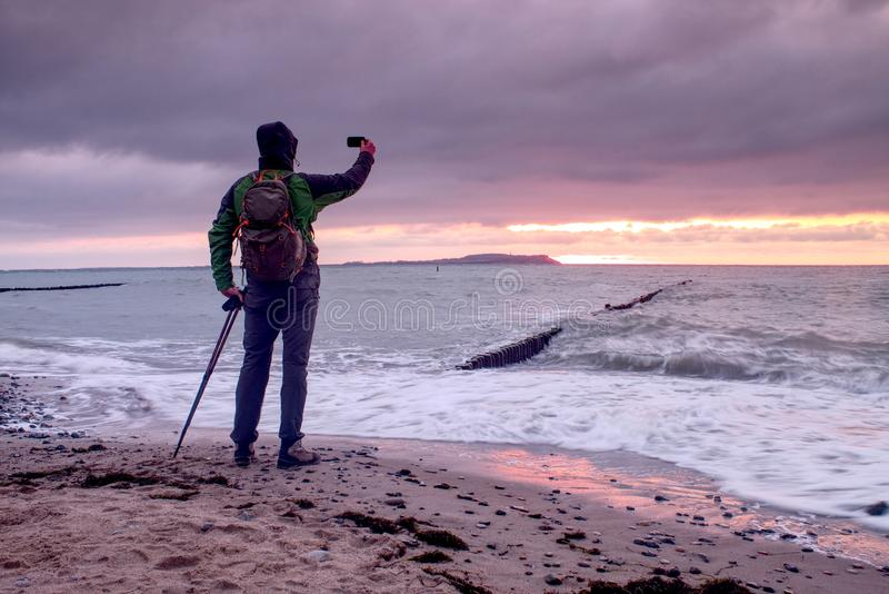 Konturn av fotografen tar fotoet av nedgången som är frånlands- med härlig solnedgånghimmel royaltyfria foton
