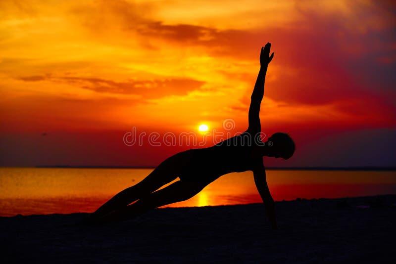 Konturn av kvinnaanseendet på yoga poserar på stranden under en fantastisk solnedgång royaltyfria bilder