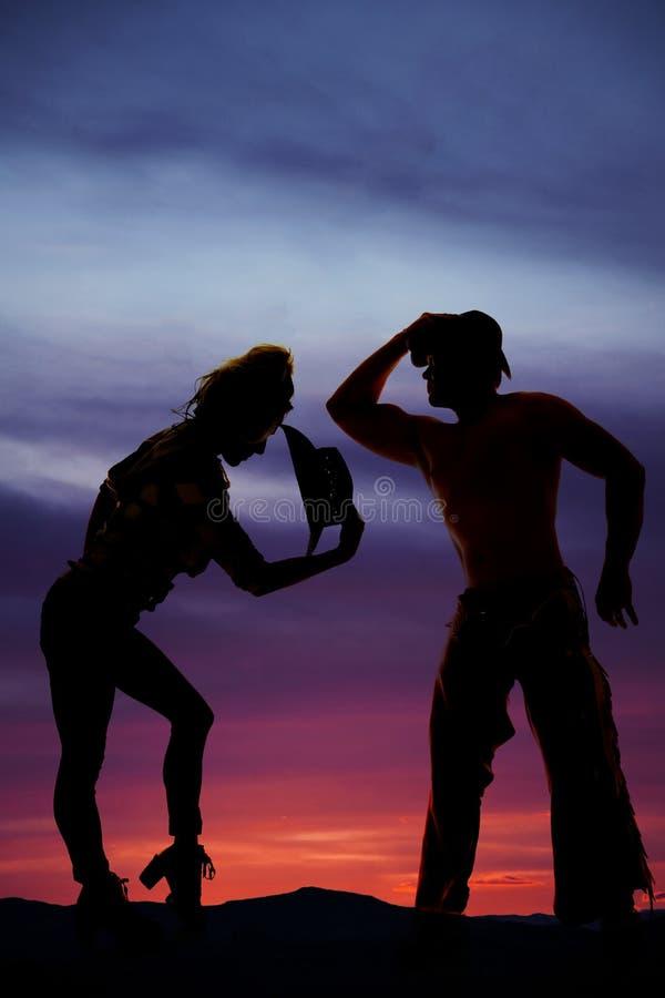 Konturn av kvinnan med cowboyhatten lutar över i solnedgången med royaltyfri bild