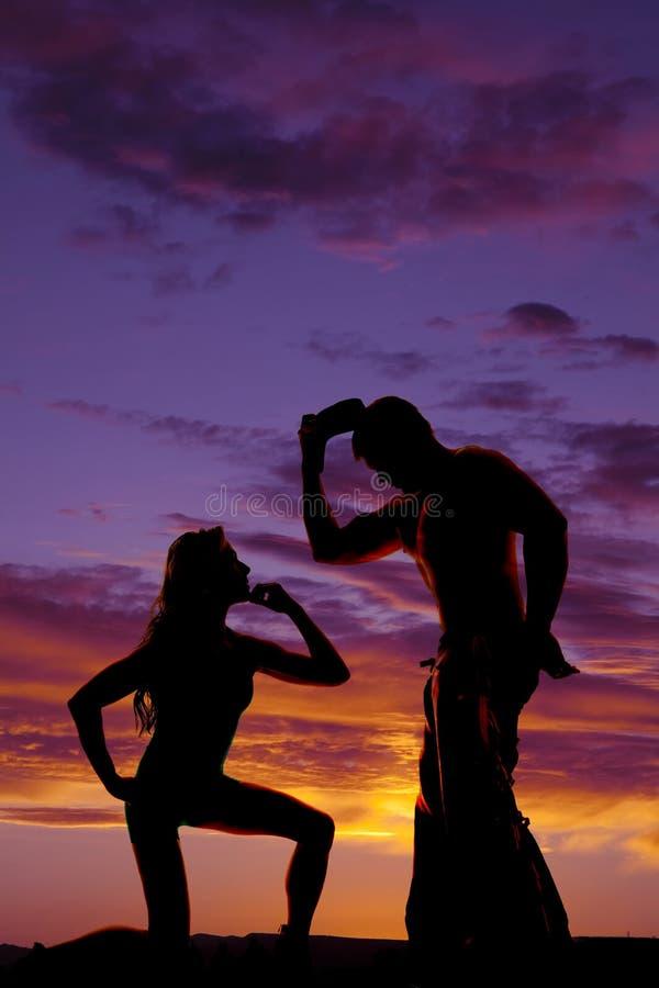 Konturn av kvinnan på knä ser upp på cowboyen royaltyfri foto