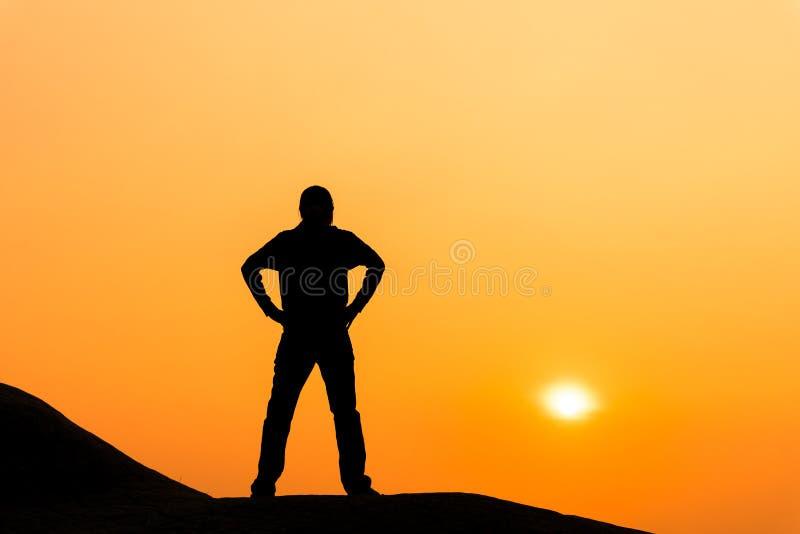 Konturn av kvinnan står och tycker om soluppgångsikt arkivbild