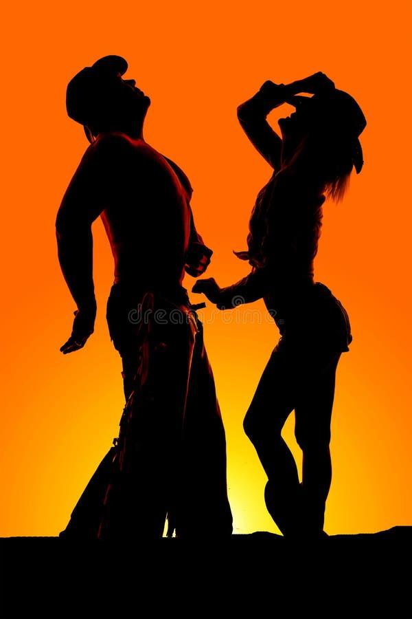 Konturn av kvinnaställningen av cowboyen båda ser upp arkivfoto