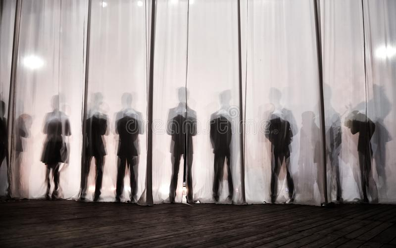 Konturn av männen bak gardinen i teatern på etapp, skuggan bak platserna är liknande till viten och blaen arkivbild