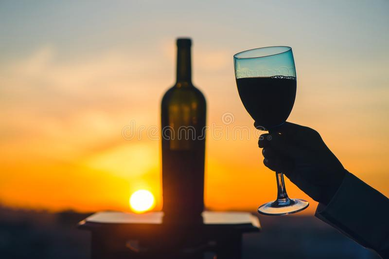 Konturn av mannen och kvinnlign räcker att rosta vin på solnedgångbakgrund Romantiska par som firar på en restaurang arkivbilder