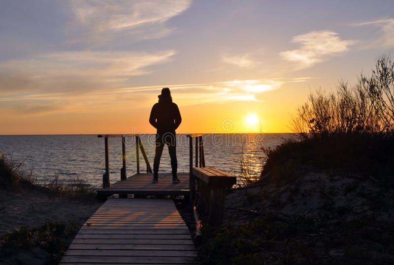 Konturn av mannen som bara står på stranden arkivfoton